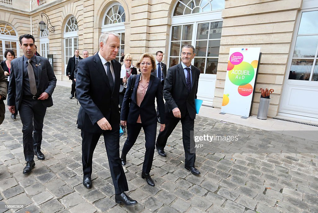 French Prime minister Jean-Marc Ayrault arrive (2ndL) arrives flanked by French Minister for Higher Education and Research Genevieve Fioraso (R), on November 26, 2012 at the elite research institution College de France in Paris, to take part in the opening of the meeting for Higher Education and Research. AFP PHOTO THOMAS SAMSON