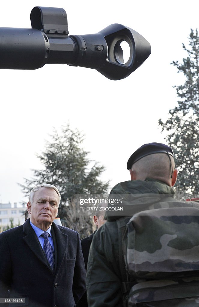 French Prime minister Jean-Marc Ayrault (L) as he reviews troops of the 2nd Engineer French Foreign Legion Regiment, on December 17, 2012 in Clermont-Ferrand, central France, during a ceremony marking the dissolution of a joint tactical bataillon that served in Afghanistan from May to November 2012. France joined the NATO coalition in late 2001 to help prop up the new government against an insurgency, which began after a US-led invasion toppled the Taliban government earlier that year for giving refuge to Osama bin Laden and his Al-Qaeda network, following the 9/11 attacks on New York and Washington. ZOCCOLAN