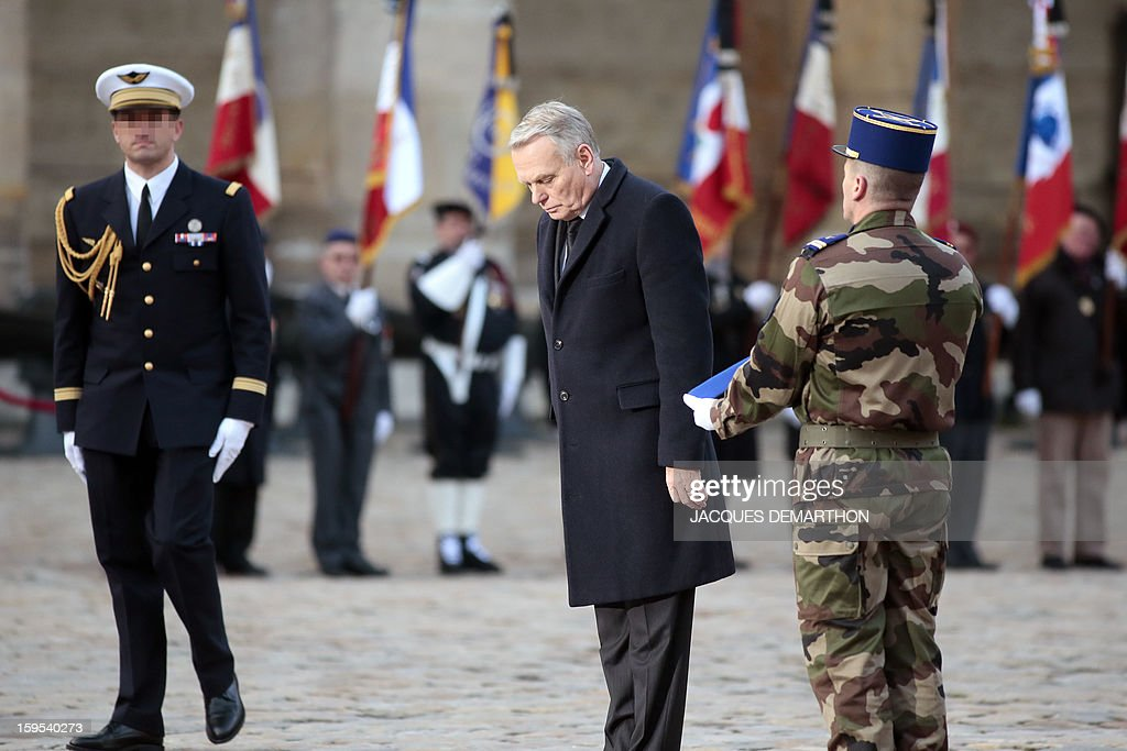 French Prime Minister Jean-Marc Ayrault bows during a funeral service for French air force lieutenant Damien Boiteux at the Invalides courtyard in Paris, on January 15, 2013. French pilot Damien Boiteux was killed on January 11 during a helicopter raid launched to support Mali ground troops in the battle for the key town of Kona, and to prevent Islamist groups controlling northern Mali from advancing toward the capital Bamako.