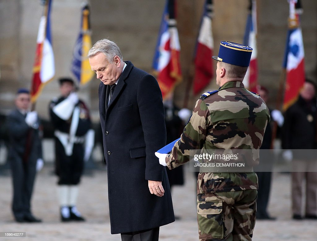 French Prime Minister Jean-Marc Ayrault bows during a funeral service for French air force lieutenant Damien Boiteux at the Invalides courtyard in Paris, on January 15, 2013. French pilot Damien Boiteux was killed on January 11 during a helicopter raid launched to support Mali ground troops in the battle for the key town of Kona, and to prevent Islamist groups controlling northern Mali from advancing toward the capital Bamako. AFP PHOTO / POOL / JACQUES DEMARTHON