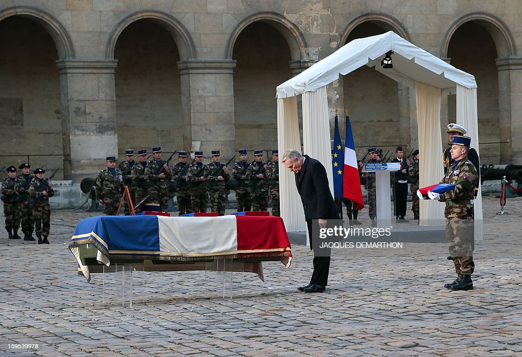 French Prime Minister Jean-Marc Ayrault bows in front of the coffin of French air force lieutenant Damien Boiteux during a funeral service at the Invalides courtyard in Paris, on January 15, 2013. French pilot Damien Boiteux was killed on January 11 during a helicopter raid launched to support Mali ground troops in the battle for the key town of Kona, and to prevent Islamist groups controlling northern Mali from advancing toward the capital Bamako.