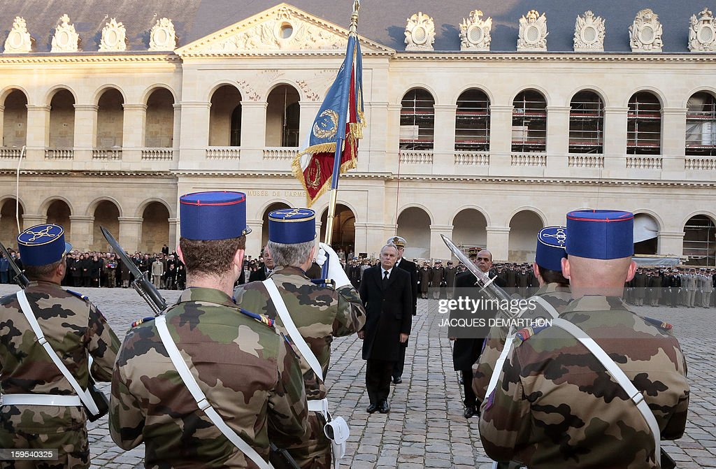 French Prime Minister Jean-Marc Ayrault (C), Defence Minister Jean-Yves Le Drian (L), junior minister for veterans affairs Kafer Arif (R), and French chief of staff Edouard Guillaud, review troops during a funeral service for French air force lieutenant Damien Boiteux at the Invalides courtyard in Paris, on January 15, 2013. French pilot Damien Boiteux was killed on January 11 during a helicopter raid launched to support Mali ground troops in the battle for the key town of Kona, and to prevent Islamist groups controlling northern Mali from advancing toward the capital Bamako.