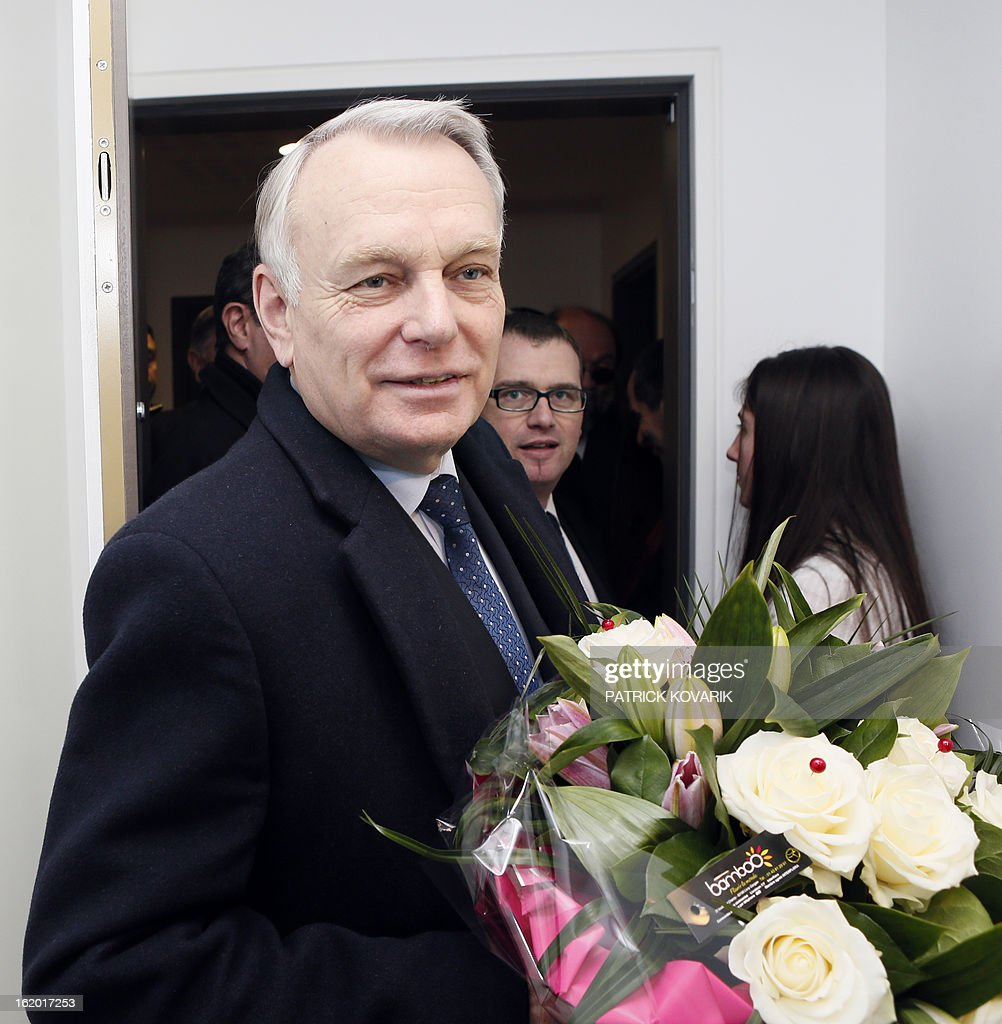 French Prime Minister Jean-Marc Ayrault (L) enters an apartment, followed by the mayor of Clichy-sous-Bois Olivier Klein (C), after receiving a bunch of flowers from a resident (R) in a residential building during a visit to Clichy-sous-Bois, northern suburb of Paris on February 18, 2013, as part of the French government's urban policy. AFP PHOTO / POOL / PATRICK KOVARIK
