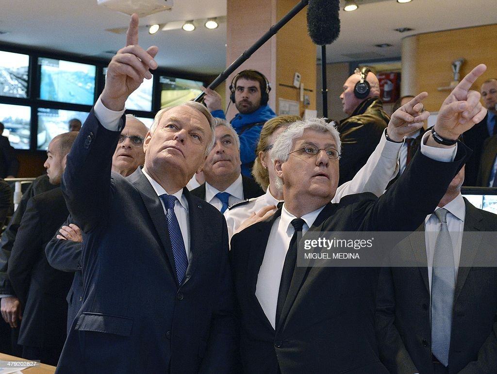 French Prime Minister Jean-Marc Ayrault (L), flanked by French Ecology Minister <a gi-track='captionPersonalityLinkClicked' href=/galleries/search?phrase=Philippe+Martin+-+Politician&family=editorial&specificpeople=12683642 ng-click='$event.stopPropagation()'>Philippe Martin</a> (R) gesture during a visit to the control directing traffic room at the Paris' prefecture on March 17, 2014. Paris today resorted to drastic measures to curb soaring pollution levels by forcing all cars with number plates ending in even numbers off the road for the first time in two decades. POOL
