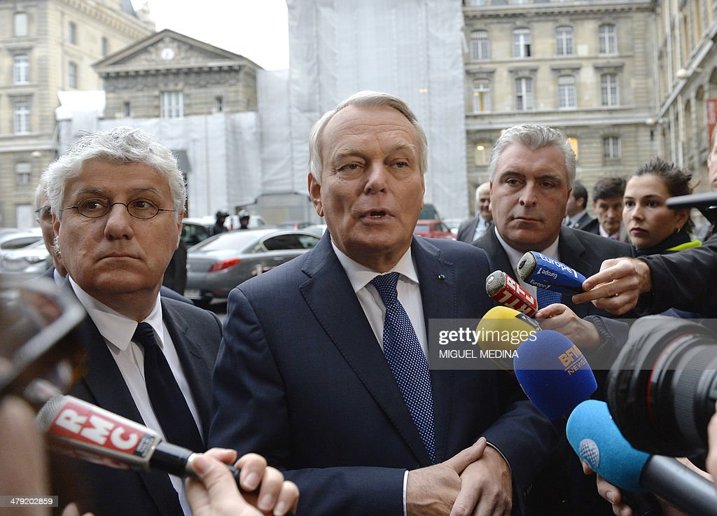 French Prime Minister Jean-Marc Ayrault (C), flanked by French Ecology Minister <a gi-track='captionPersonalityLinkClicked' href=/galleries/search?phrase=Philippe+Martin+-+Politician&family=editorial&specificpeople=12683642 ng-click='$event.stopPropagation()'>Philippe Martin</a> (L) and French Junior Minister for Transports and Maritime Economy, Frederic Cuvillier (R) speak to the press during a visit to the control directing traffic room at the Paris' Prefecture on March 17, 2014. Paris today resorted to drastic measures to curb soaring pollution levels by forcing all cars with number plates ending in even numbers off the road for the first time in two decades.