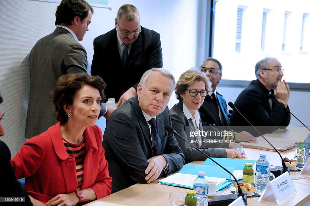 French Prime Minister Jean-Marc Ayrault (C), flanked by Marisol Touraine, French Social Affairs and Health Minister (C,L) and Genevieve Fioraso, French Minister for Higher Education and Research (C,R) pose on February 8, 2013 prior to a meeting with members of a neurosurgery unit at the Couple Enfant Hospital in Grenoble. AFP PHOTO / JEAN-PIERRE CLATOT