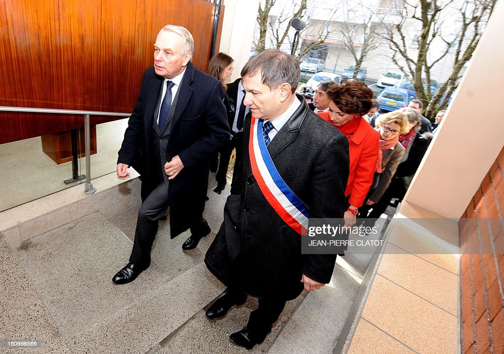 French Prime Minister Jean-Marc Ayrault (L) flanked by mayor Rene Proby, is pictured prior to a meeting with employees of the Pole Sante Universitaire (Universitary Health Center) on February 8, 2013 in Saint-Martin d'Heres, French Alps.
