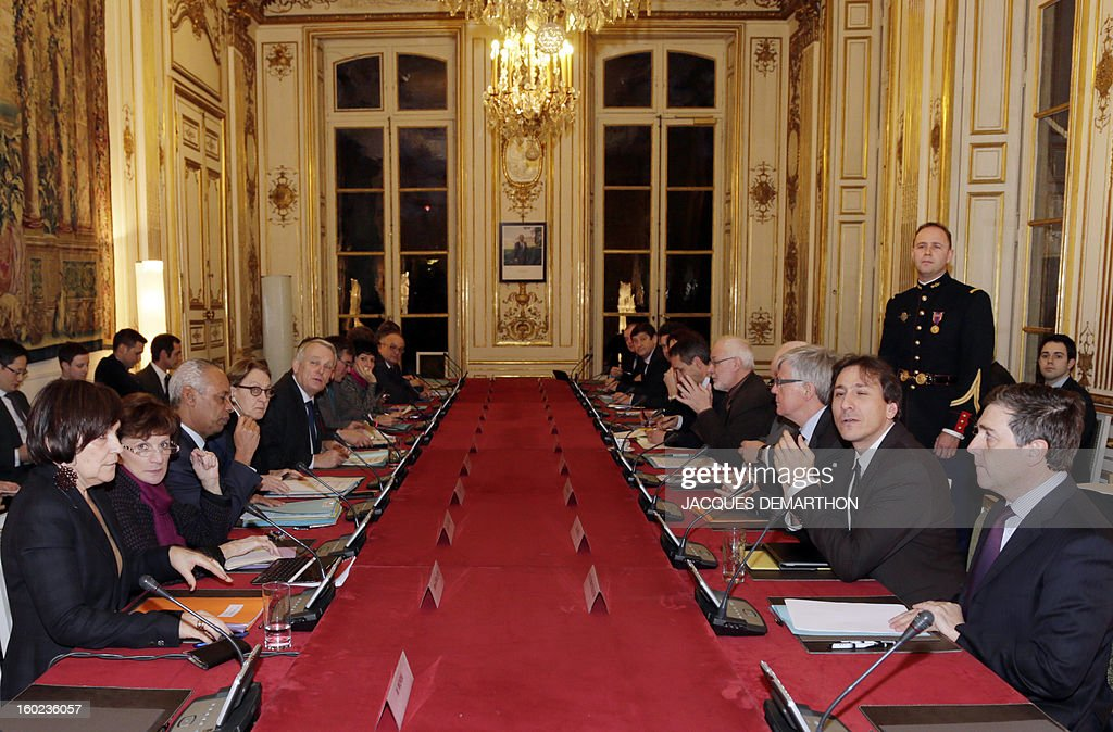 French Prime Minister Jean-Marc Ayrault (5th), flanked by ministers (left row), heads, on January 28, 2013, in Paris, at the Hotel Matignon, the Prime Minister official residence, a meeting for the creation of a working committee between French State and departements of France. Right row, a delegation of local representatives.