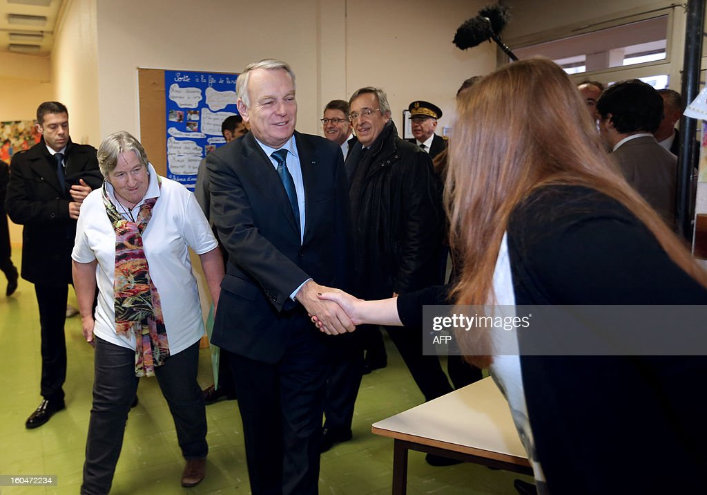 French Prime Minister Jean-Marc Ayrault (C), flanked by school director, shakes hands with a teacher upon his arrival at the Coquibus primary school for a visit, on February 1, 2013 in Evry, outside Paris. AFP PHOTO / THOMAS SAMSON