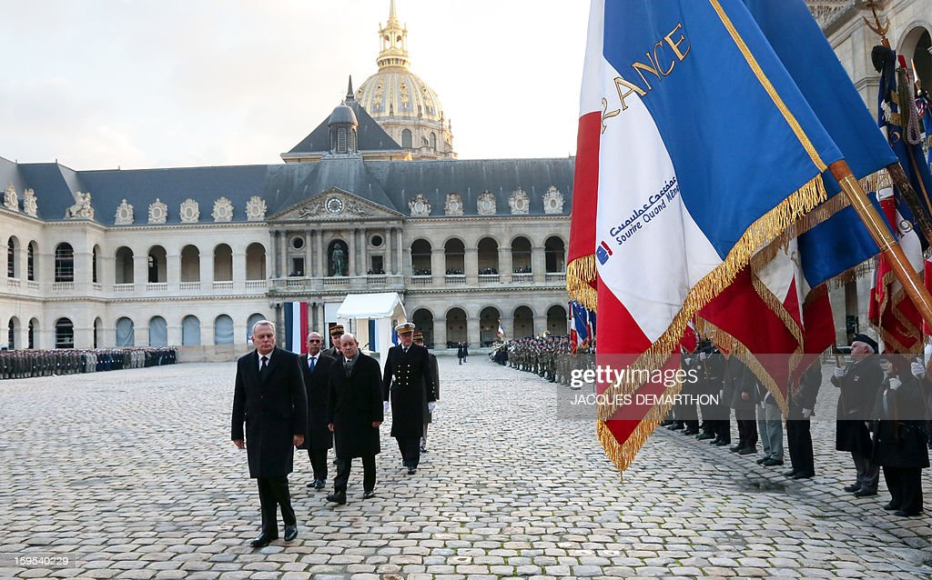 French Prime Minister Jean-Marc Ayrault (front), followed by Defence Minister Jean-Yves Le Drian, junior minister for veterans affairs Kafer Arif, and French chief of staff Edouard Guillaud, reviews troops during a funeral service for French air force lieutenant Damien Boiteux at the Invalides courtyard in Paris, on January 15, 2013. French pilot Damien Boiteux was killed on January 11 during a helicopter raid launched to support Mali ground troops in the battle for the key town of Kona, and to prevent Islamist groups controlling northern Mali from advancing toward the capital Bamako.