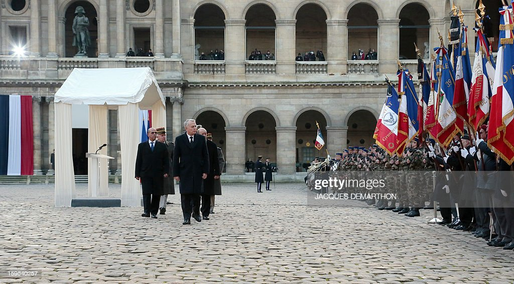 French Prime Minister Jean-Marc Ayrault (front), followed by Defence Minister Jean-Yves Le Drian, junior minister for veterans affairs Kafer Arif, and French chief of staff Edouard Guillaud, reviews troops during a funeral service for French air force lieutenant Damien Boiteux at the Invalides courtyard in Paris, on January 15, 2013. French pilot Damien Boiteux was killed on January 11 during a helicopter raid launched to support Mali ground troops in the battle for the key town of Kona, and to prevent Islamist groups controlling northern Mali from advancing toward the capital Bamako. AFP PHOTO / POOL / JACQUES DEMARTHON