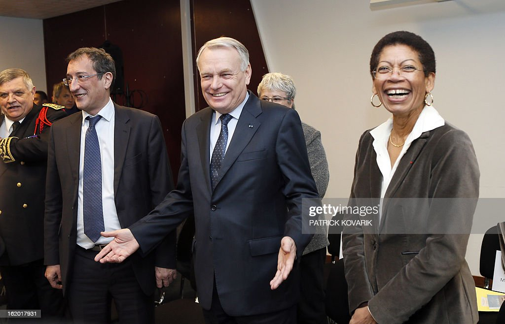 French Prime Minister Jean-Marc Ayrault (C), French Junior Minister for Cities Francois Lamy (2ndL) and French Junior Minister for Educational Success George Pau-Langevin share a laugh before taking part in a meeting with students of the Alfred Nobel High school, during a visit in Clichy-sous-Bois, northern suburb of Paris, on February 18, 2013, as part of the French government's urban policy. AFP PHOTO / PATRICK KOVARIK