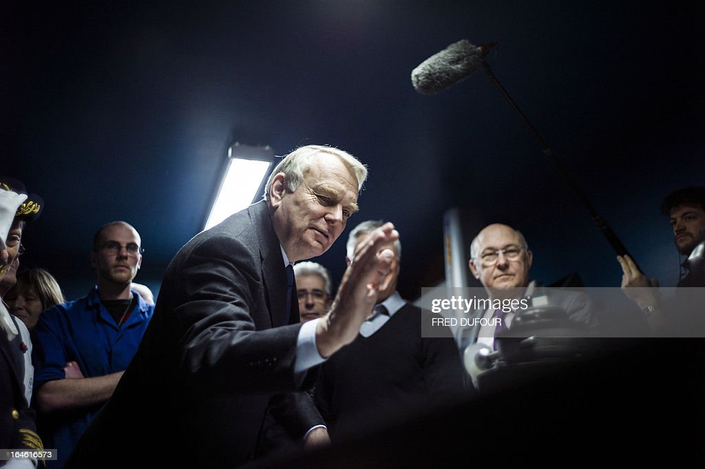 French Prime Minister Jean-Marc Ayrault (C) gestures during a visit focused on employment on March 25, 2013 in Mitry-Mory, North East of Paris, at the OPA-OPTICAD, an optical production and assembling company specialized in lazer and optical systems.