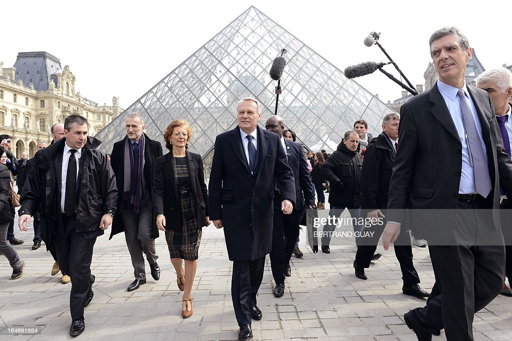 French Prime Minister Jean-Marc Ayrault (C), his wife Brigitte (3rdL) and Louvre President Henri Loyrette (1stR) leave on March 26, 2013 after a visit of the exhibition 'De l'Allemagne, 1800-1939 - From Friedrich to Beckmann' at the Louvre museum in Paris .