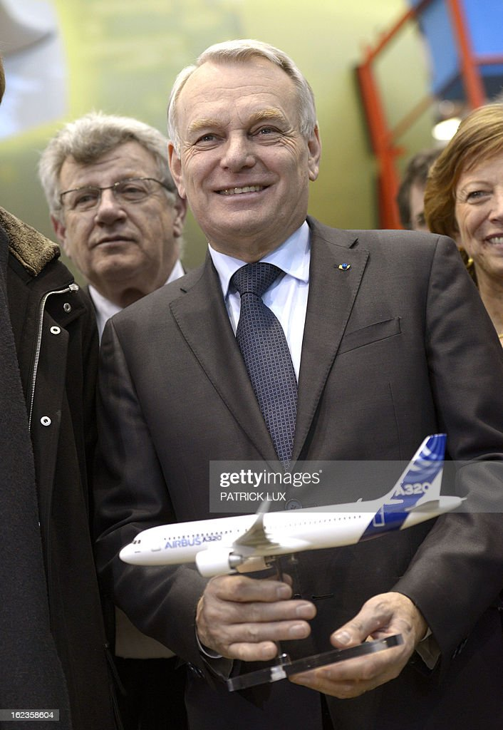 French Prime Minister Jean-Marc Ayrault holds a miniature of the A320 airplane during a visit of the final A320 airplane assembly line on February 22, 2013 in Hamburg. Ayrault is on a visit to Hamburg participating on the traditional Matthiae-Mahl.