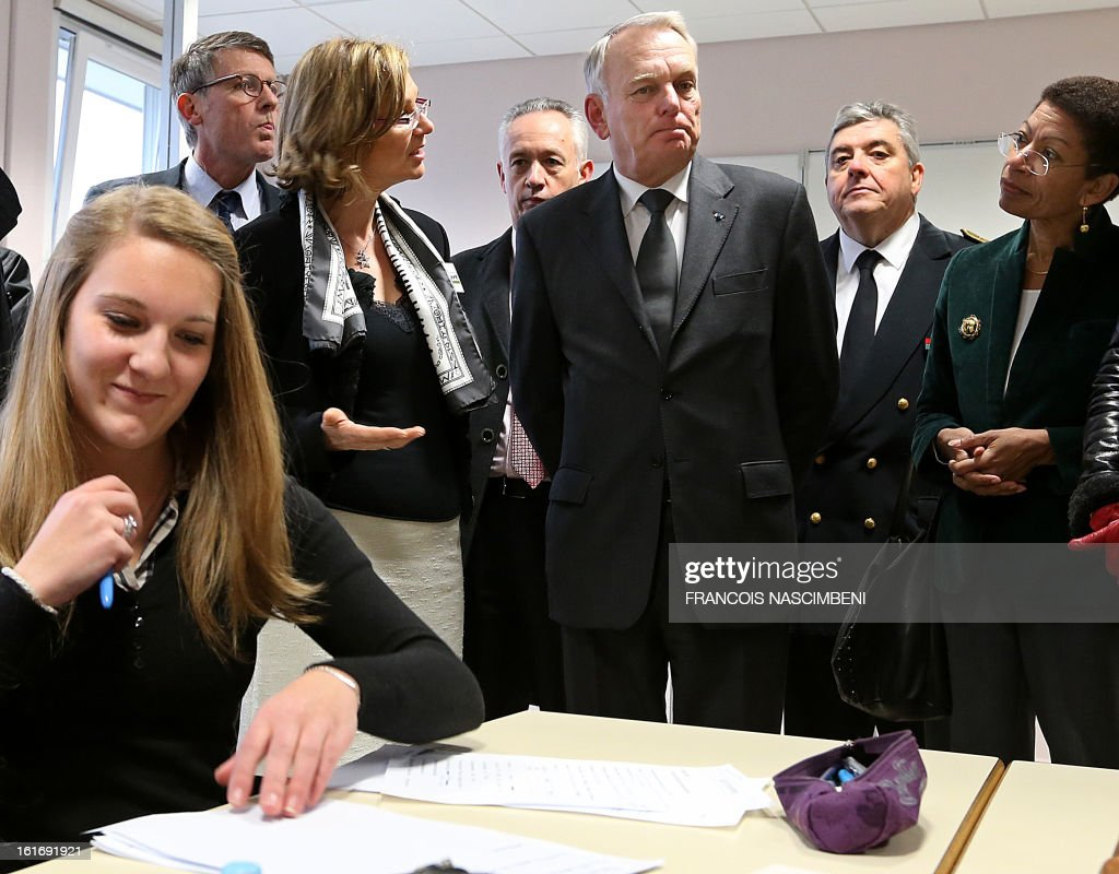 French Prime Minister Jean-Marc Ayrault (C) listens to explanations, accompanied by French Education Minister Vincent Peillon (2ndL, background) and French Junior Minister for Educational Success George Pau-Langevin (R) during a visit on February 14, 2013 to the Colbert high school in Reims, eastern France, before signing agreements for the 'Future Professional Jobs' (Emploi d'Avenir Professionnel, EAP in French).