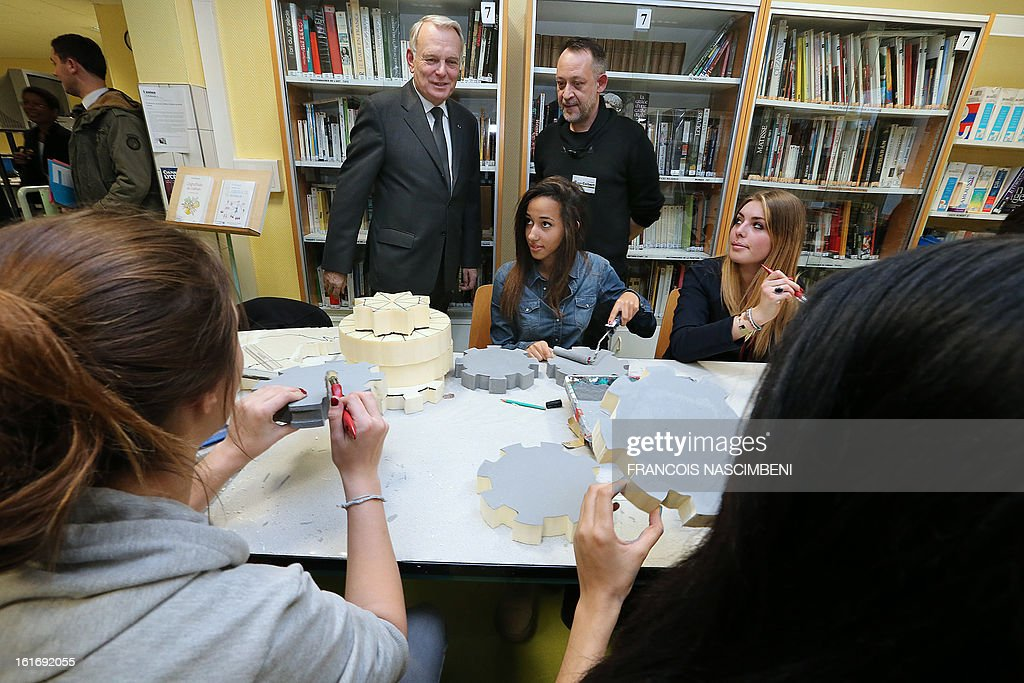 French Prime Minister Jean-Marc Ayrault (C) look at pupils learning handcrafts during a visit on February 14, 2013 to the Colbert high school in Reims, eastern France, before signing agreements for the 'Future Professional Jobs' (Emploi d'Avenir Professionnel, EAP in French).