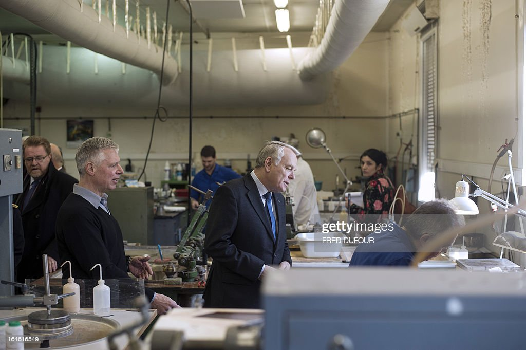 French Prime Minister Jean-Marc Ayrault (C) looks at an employee at work during a visit focused on employment on March 25, 2013 in Mitry-Mory, North East of Paris, at the OPA-OPTICAD, an optical production and assembling company specialized in lazer and optical systems.