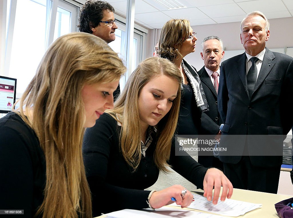 French Prime Minister Jean-Marc Ayrault (R) looks at pupils as he listens to explanations during a visit on February 14, 2013 to the Colbert high school in Reims, eastern France, before signing agreements for the 'Future Professional Jobs' (Emploi d'Avenir Professionnel, EAP in French).