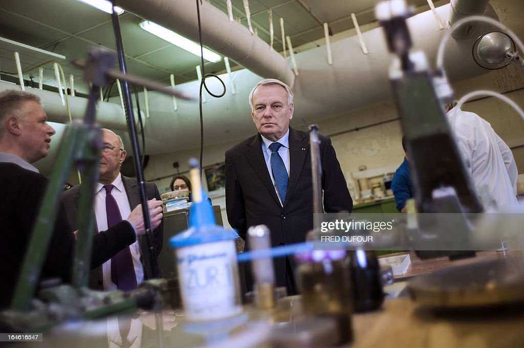 French Prime Minister Jean-Marc Ayrault (C) looks on during a visit focused on employment on March 25, 2013 in Mitry-Mory, North East of Paris, at the OPA-OPTICAD, an optical production and assembling company specialized in lazer and optical systems.