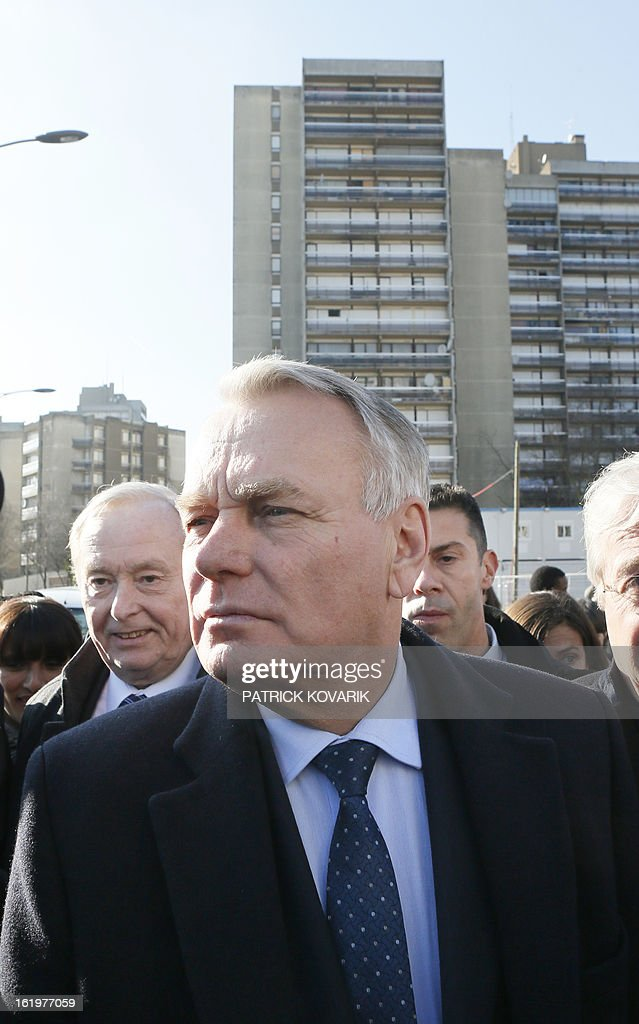 French Prime Minister Jean-Marc Ayrault (C) looks on, followed by the former mayor of Clichy-sous-Bois, Claude Dilain (L) on February 18, 2013 during his visit to Clichy-sous-Bois, northern suburb of Paris, as part of the French government's urban policy.