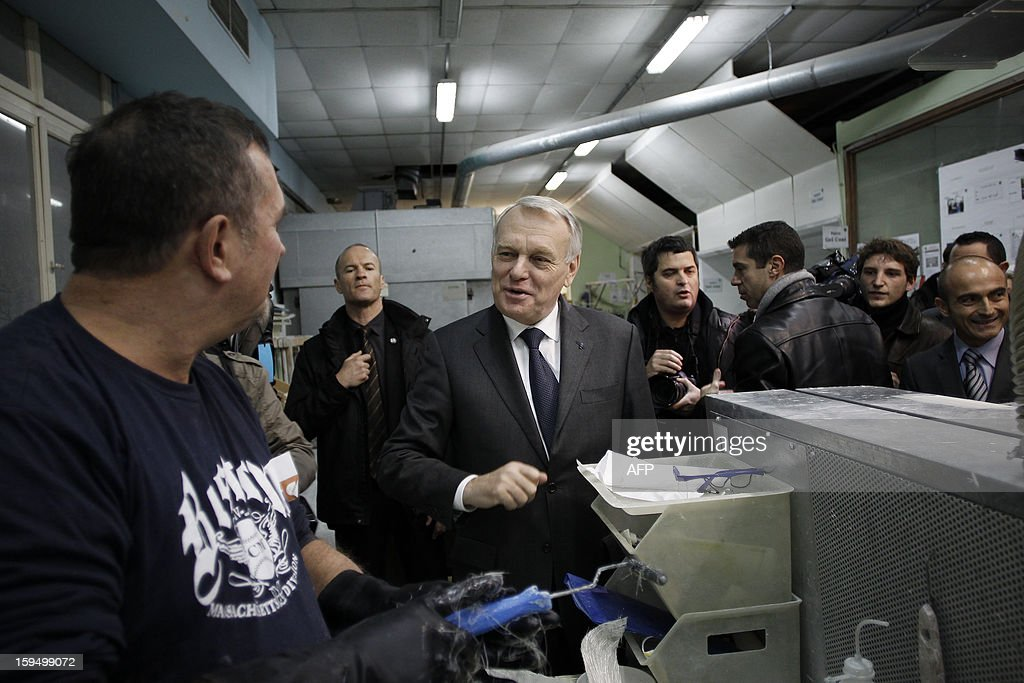 French Prime Minister Jean-Marc Ayrault (C) meets people as he visits a workshop in a center for adult learning (Afpa - formation pour adultes), on January 14, 2013 in Caen, Normandy.