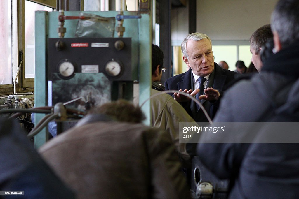 French Prime Minister Jean-Marc Ayrault (C) meets people as he visits a workshop in a center for adult learning (Afpa - formation pour adultes), on January 14, 2013 in Caen, Normandy. AFP PHOTO / CHARLY TRIBALLEAU