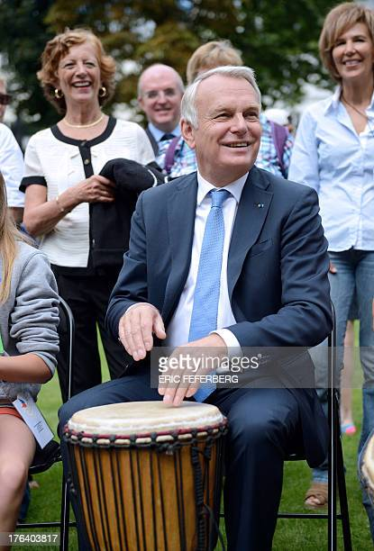 French Prime Minister JeanMarc Ayrault plays djembe as his wife Brigitte looks on during a picnic party with children who cannot afford to go on...