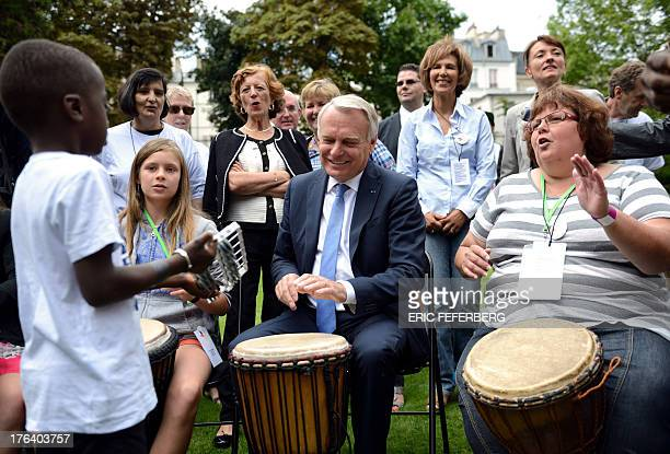 French Prime Minister JeanMarc Ayrault plays djembe during a picnic party with children who cannot afford to go on holidays in the garden of his...