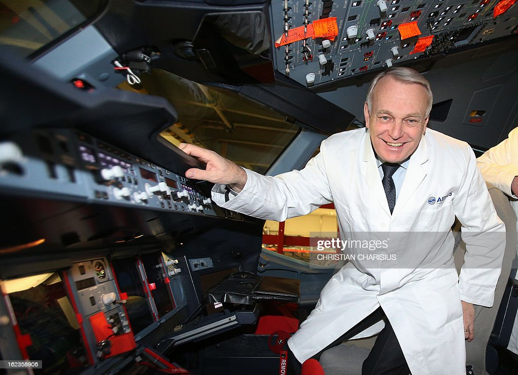 French Prime Minister Jean-Marc Ayrault poses inside a cockpit of an A380 airbus of Korean airlines 'Korean Air' during a visit to the final assembly line of the Airbus A380 on February 22, 2013 in Hamburg. Ayrault is on a visit to Hamburg participating on the traditional Matthiae-Mahl.