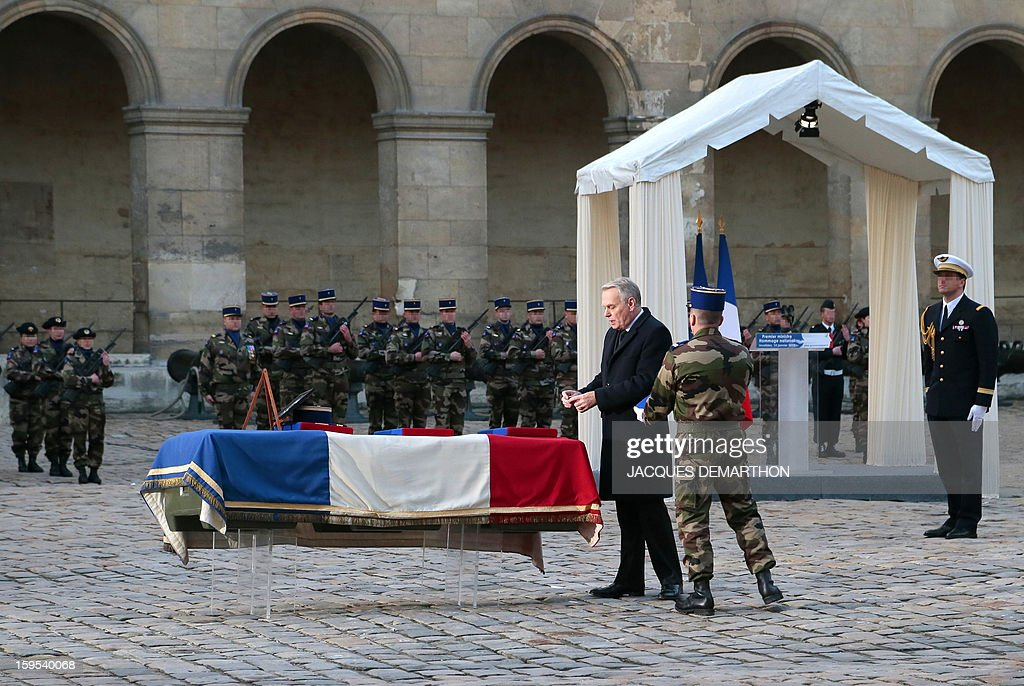 French Prime Minister Jean-Marc Ayrault posthumously awards as knight in the order of the Legion d'Honneur French air force lieutenant Damien Boiteux during a funeral service at the Invalides courtyard in Paris, on January 15, 2013. French pilot Damien Boiteux was killed on January 11 during a helicopter raid launched to support Mali ground troops in the battle for the key town of Kona, and to prevent Islamist groups controlling northern Mali from advancing toward the capital Bamako.