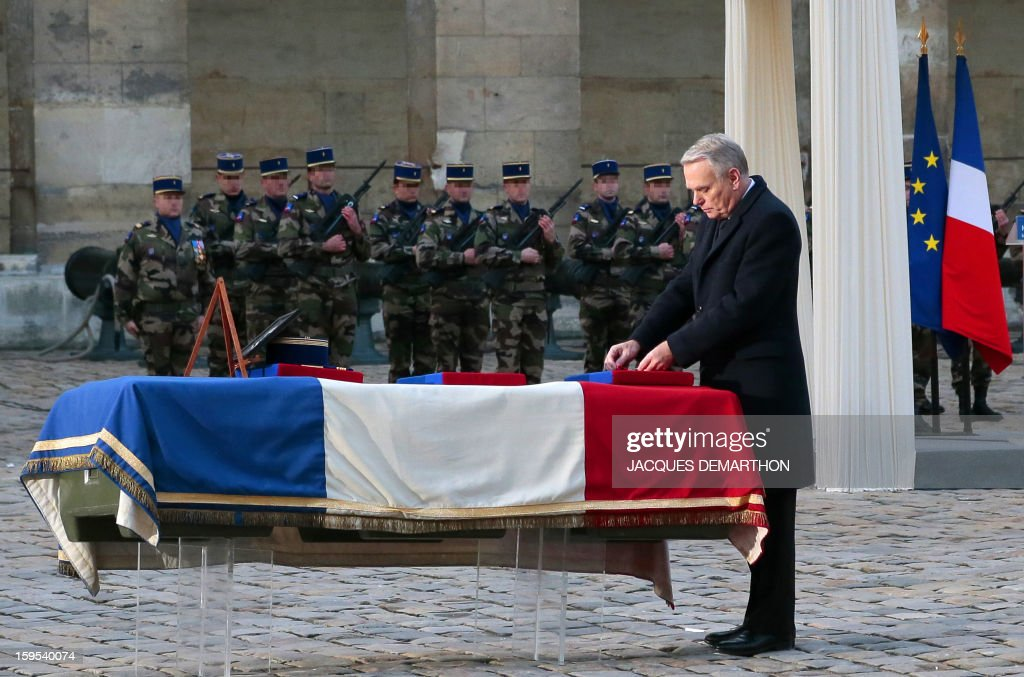 French Prime Minister Jean-Marc Ayrault posthumously awards as knight in the order of the Legion d'Honneur French air force lieutenant Damien Boiteux during a funeral service at the Invalides courtyard in Paris, on January 15, 2013. French pilot Damien Boiteux was killed on January 11 during a helicopter raid launched to support Mali ground troops in the battle for the key town of Kona, and to prevent Islamist groups controlling northern Mali from advancing toward the capital Bamako. AFP PHOTO / POOL / JACQUES DEMARTHON