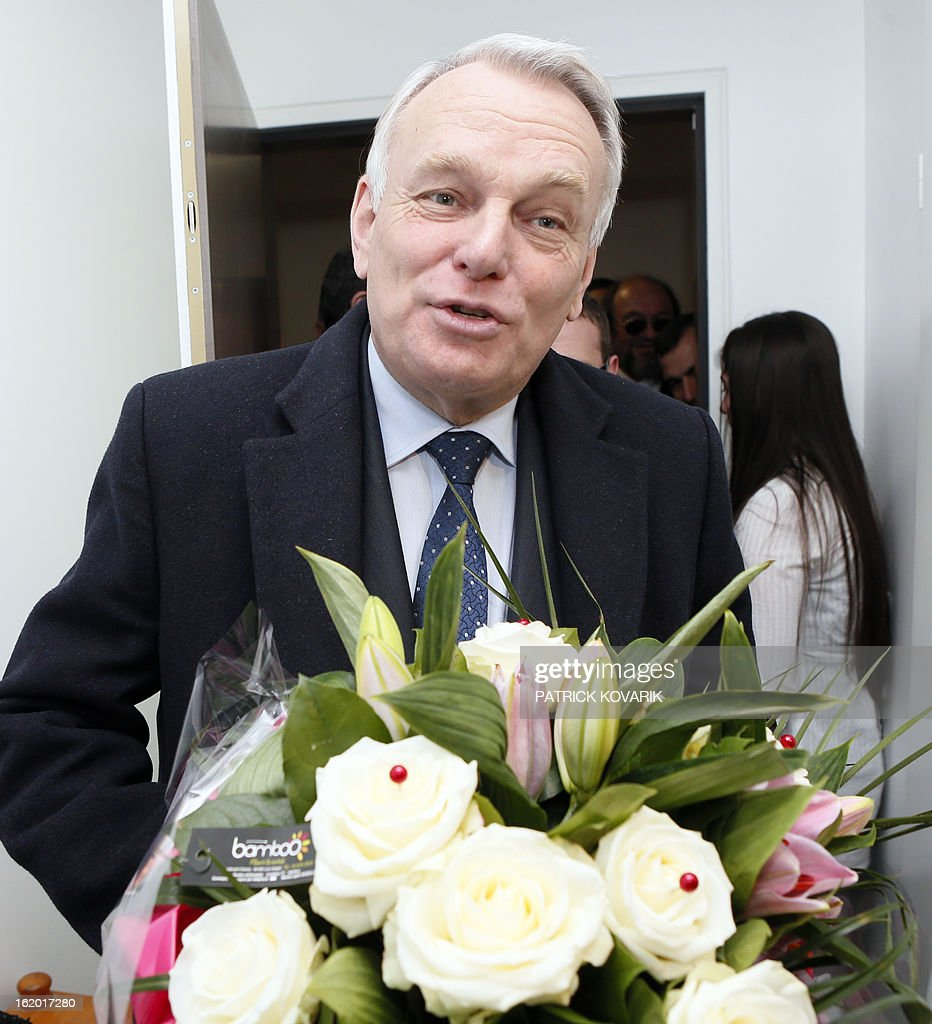 French Prime Minister Jean-Marc Ayrault reacts as he enters an apartment after receiving a bunch of flowers from a resident (R) in a residential building during a visit to Clichy-sous-Bois, northern suburb of Paris on February 18, 2013, as part of the French government's urban policy. AFP PHOTO / POOL / PATRICK KOVARIK