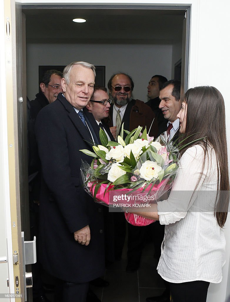 French Prime Minister Jean-Marc Ayrault (L) receives a bunch of flowers from a resident in a residential building during a visit to Clichy-sous-Bois, northern suburb of Paris on February 18, 2013, as part of the French government's urban policy.