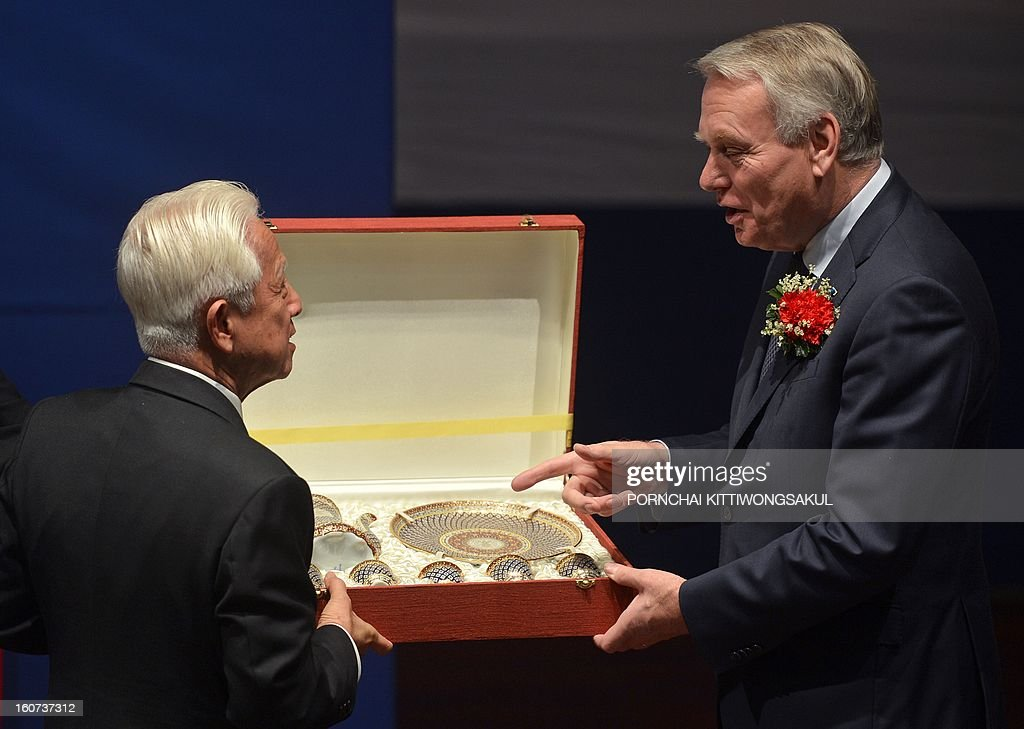 French Prime Minister Jean-Marc Ayrault (R) receives a souvenir from president of Thammasat University Council, Professor Noranit Setabutr (L), after giving a speech during a visit to Thammasat University in Bangkok on February 5, 2013. Ayrault is on two-day official visit to Thailand.
