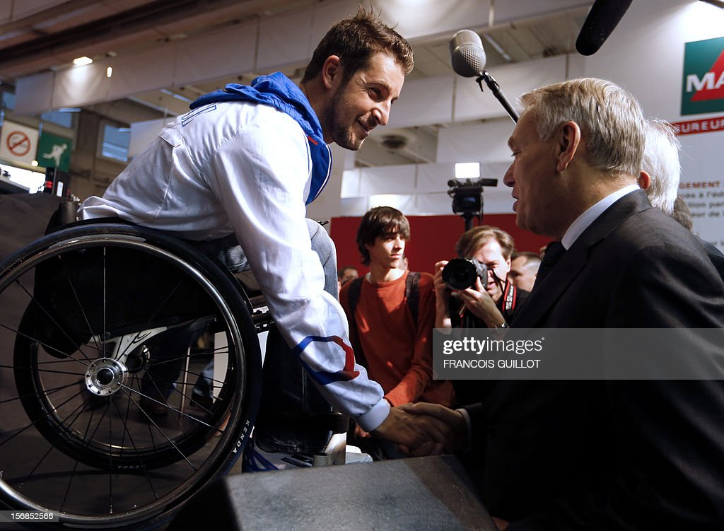 French Prime Minister Jean-Marc Ayrault (R) shakes hands with a youth during an European education convention in Paris on November 23, 2012.