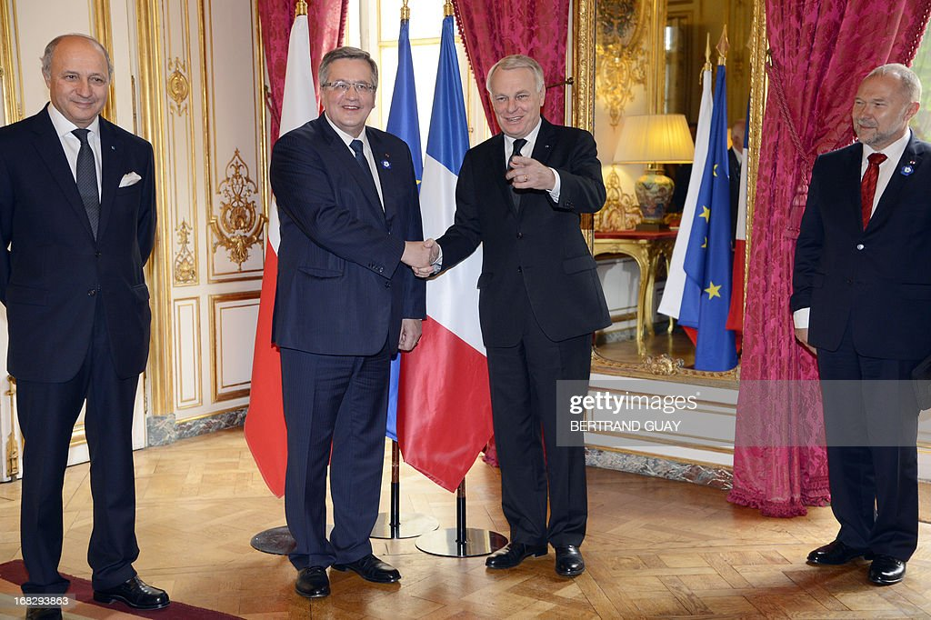 French Prime Minister Jean-Marc Ayrault (2nd R) shakes hands with Polish President Bronislaw Komorowski (2nd L), before a lunch at the Hotel Matinon in Paris, on May 8, 2013. At left French Minister of Foreign Affairs Laurent Fabius. AFP PHOTO POOL / BERTRAND GUAY