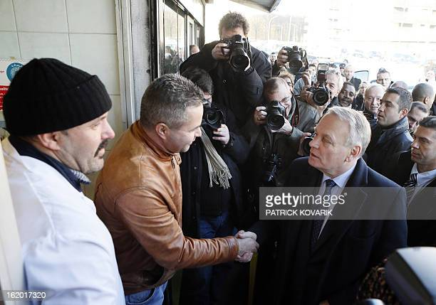 French Prime Minister JeanMarc Ayrault shakes hands with residents during a visit to ClichysousBois northern suburb of Paris on February 18 as part...