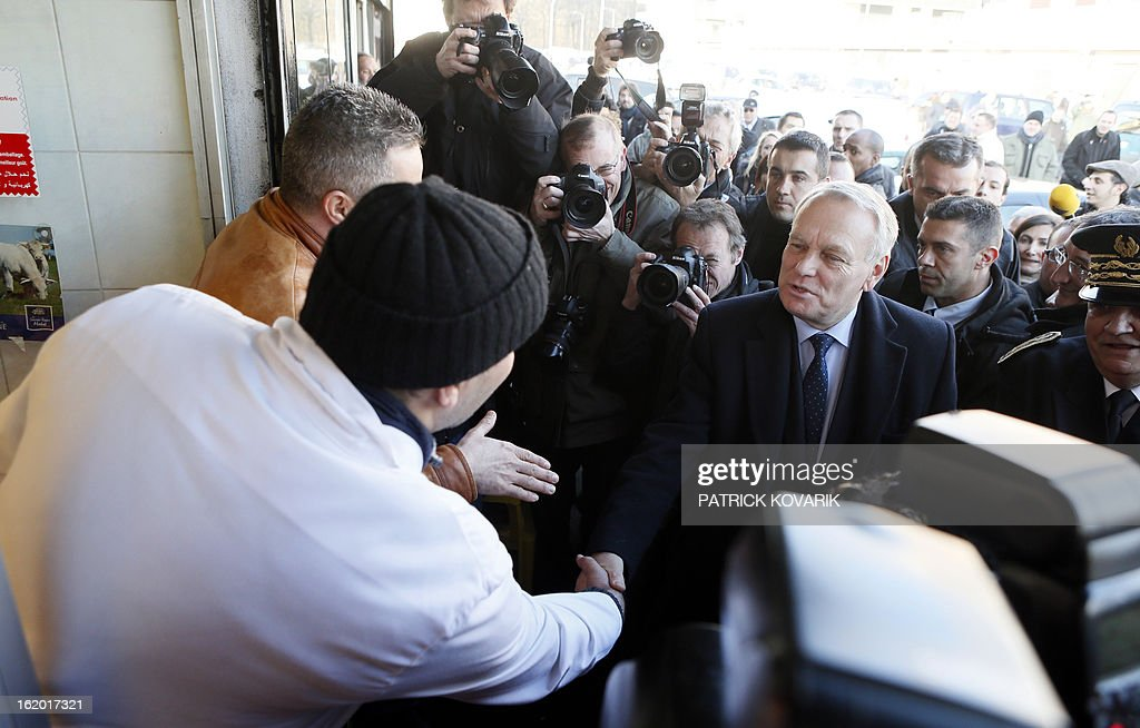 French Prime Minister Jean-Marc Ayrault (R) shakes hands with residents during a visit to Clichy-sous-Bois, northern suburb of Paris on February 18, 2013, as part of the French government's urban policy.