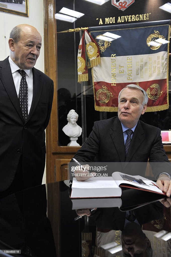 French Prime minister Jean-Marc Ayrault (R) signs the guests' book of the regiment, next to French Defence Minister Jean-Yves Le Drian (L) after a ceremony marking the dissolution of a joint tactical bataillon that served in Afghanistan from May to November 2012, on December 17, 2012 in Clermont-Ferrand.