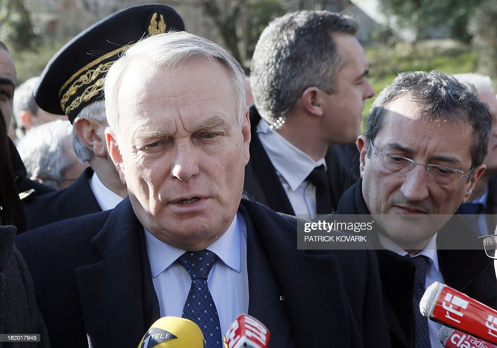 French Prime Minister Jean-Marc Ayrault (L) speaks to journalists next to French Junior Minister for Cities Francois Lamy (L) during a visit to Clichy-sous-Bois, northern suburb of Paris, on February 18, 2013, as part of the French government's urban policy. AFP PHOTO / PATRICK KOVARIK