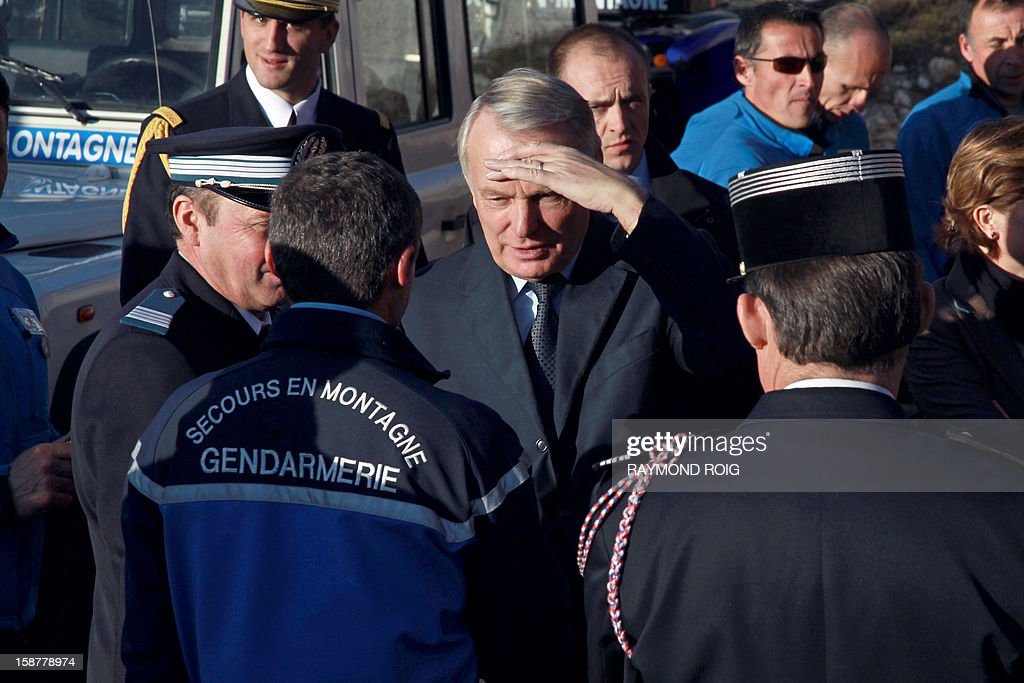 French Prime minister Jean-Marc Ayrault (C) speaks with gendarmes and police officers in charge of mountain rescue operations during a visit at the Font-Romeu gendarmes headquarters, southern France, on December 28, 2012. AFP PHOTO / RAYMOND