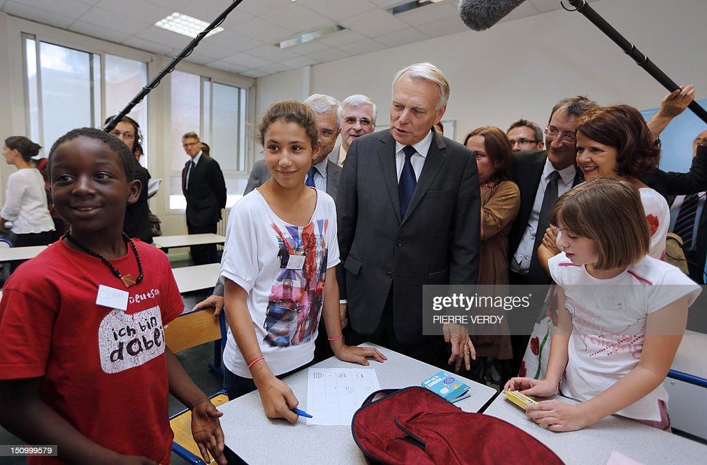 French Prime Minister Jean-Marc Ayrault (C) speaks with pupils, on August 30, 2012 at the Jean Zay college in Bondy, as part of a visit focused on education.