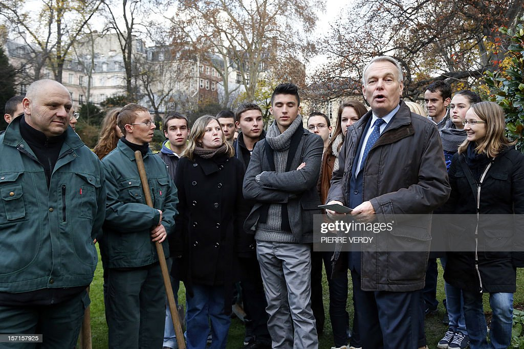 French Prime Minister Jean-Marc Ayrault (R) speaks with students during a tree planting on the grounds of Hotel Matignon in Paris on November 29, 2012.