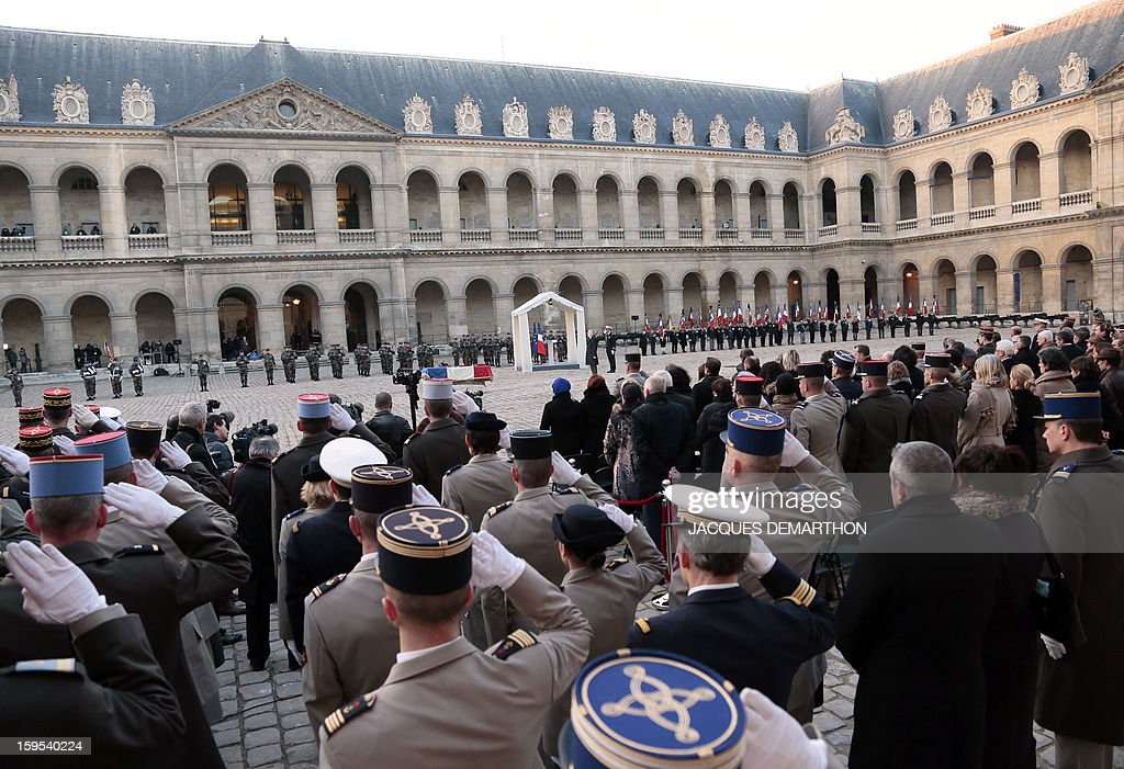 French Prime Minister Jean-Marc Ayrault (C) stands during a funeral service for French air force lieutenant Damien Boiteux at the Invalides courtyard in Paris, on January 15, 2013. French pilot Damien Boiteux was killed on January 11 during a helicopter raid launched to support Mali ground troops in the battle for the key town of Kona, and to prevent Islamist groups controlling northern Mali from advancing toward the capital Bamako. AFP PHOTO / POOL / JACQUES DEMARTHON