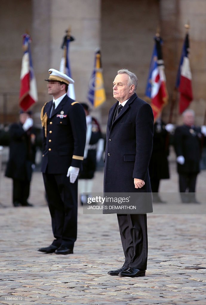 French Prime Minister Jean-Marc Ayrault stands during a funeral service for French air force lieutenant Damien Boiteux at the Invalides courtyard in Paris, on January 15, 2013. French pilot Damien Boiteux was killed on January 11 during a helicopter raid launched to support Mali ground troops in the battle for the key town of Kona, and to prevent Islamist groups controlling northern Mali from advancing toward the capital Bamako. AFP PHOTO / POOL / JACQUES DEMARTHON