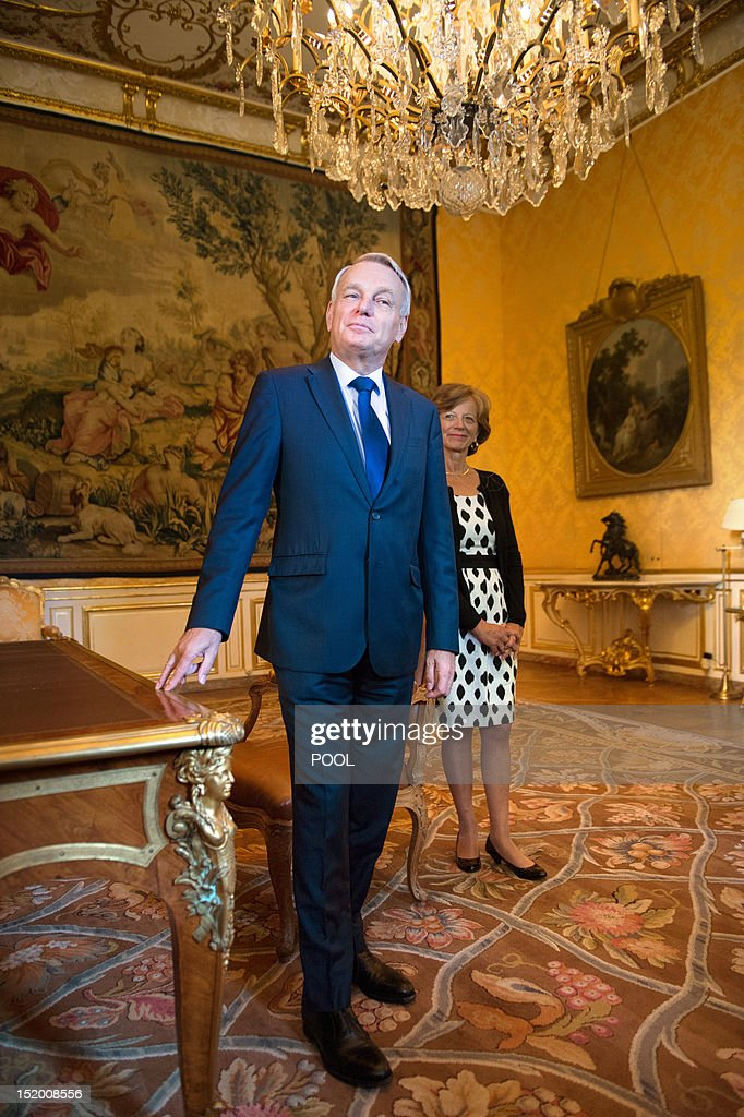 French Prime Minister Jean-Marc Ayrault (L) stands next to a desk, accompanied by his wife Brigitte prior to welcoming visitors in the yellow reception room (Salon Jaune in French), on September 15, 2012, at the Hotel Matignon, French Prime Minister's official residence, in Paris, during the 29th edition of France's European heritage open days. France opens the doors of its state buildings, some usually forbidden to the public, during these European heritage days until September 16. As part of this year's edition, Hotel Matignon unveils the desk of French socialist statesman and former Prime Minister Leon Blum (1872-1950) displayed in the yellow reception room, on which Blum signed the Matignon Agreements on June 1936.