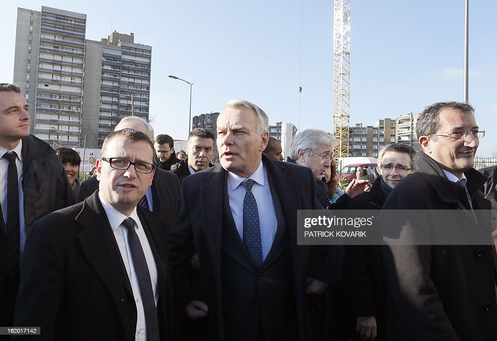French Prime Minister Jean-Marc Ayrault (C), surrounded by the mayor of Clichy-sous-Bois Olivier Klein (L) and French Junior Minister for Cities Francois Lamy, takes part in a visit to Clichy-sous-Bois, northern suburb of Paris on February 18, 2013, as part of the French government's urban policy.
