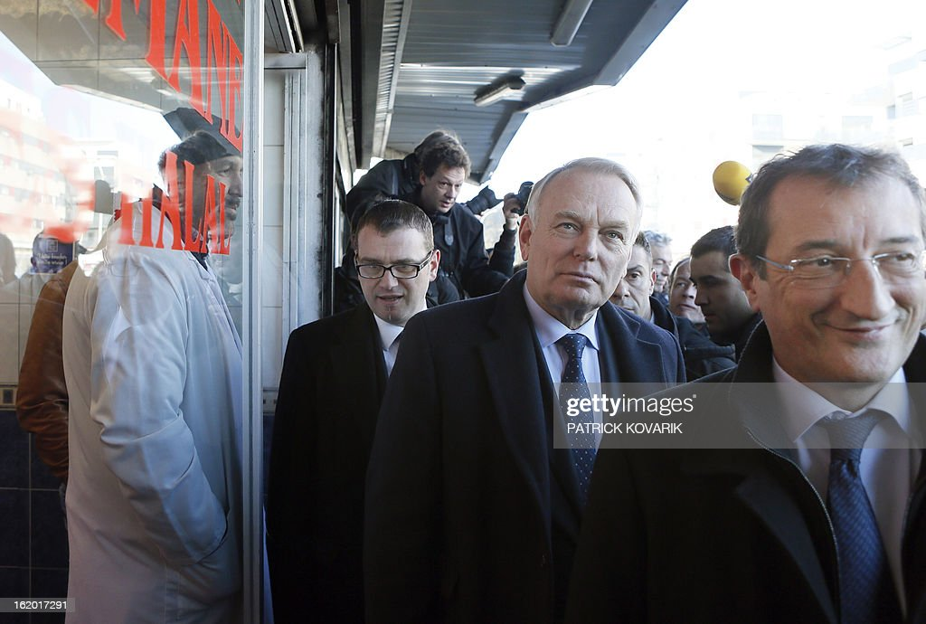 French Prime Minister Jean-Marc Ayrault (C), surrounded by the mayor of Clichy-sous-Bois Olivier Klein (L) and French Junior Minister for Cities Francois Lamy(R) takes part in a visit to Clichy-sous-Bois, northern suburb of Paris on February 18, 2013, as part of the French government's urban policy.