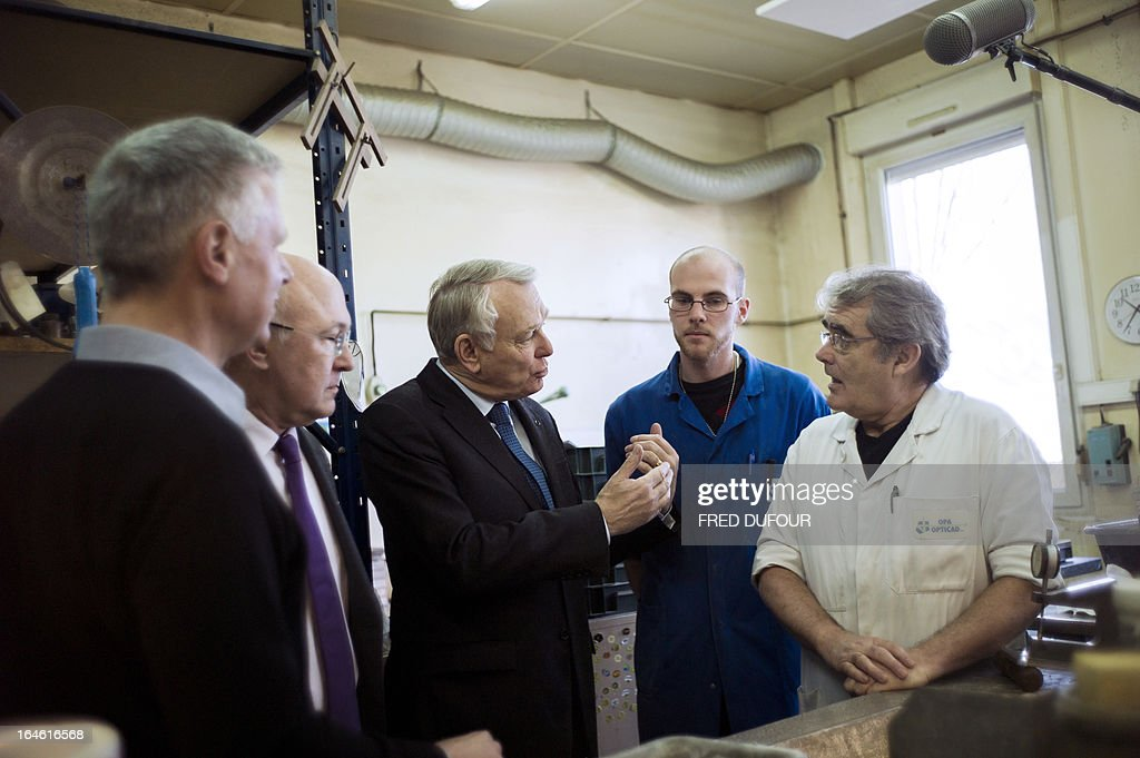 French Prime Minister Jean-Marc Ayrault (C) talks to an employee during a visit focused on employment on March 25, 2013 in Mitry-Mory, North East of Paris, at the OPA-OPTICAD, an optical production and assembling company specialized in lazer and optical systems.